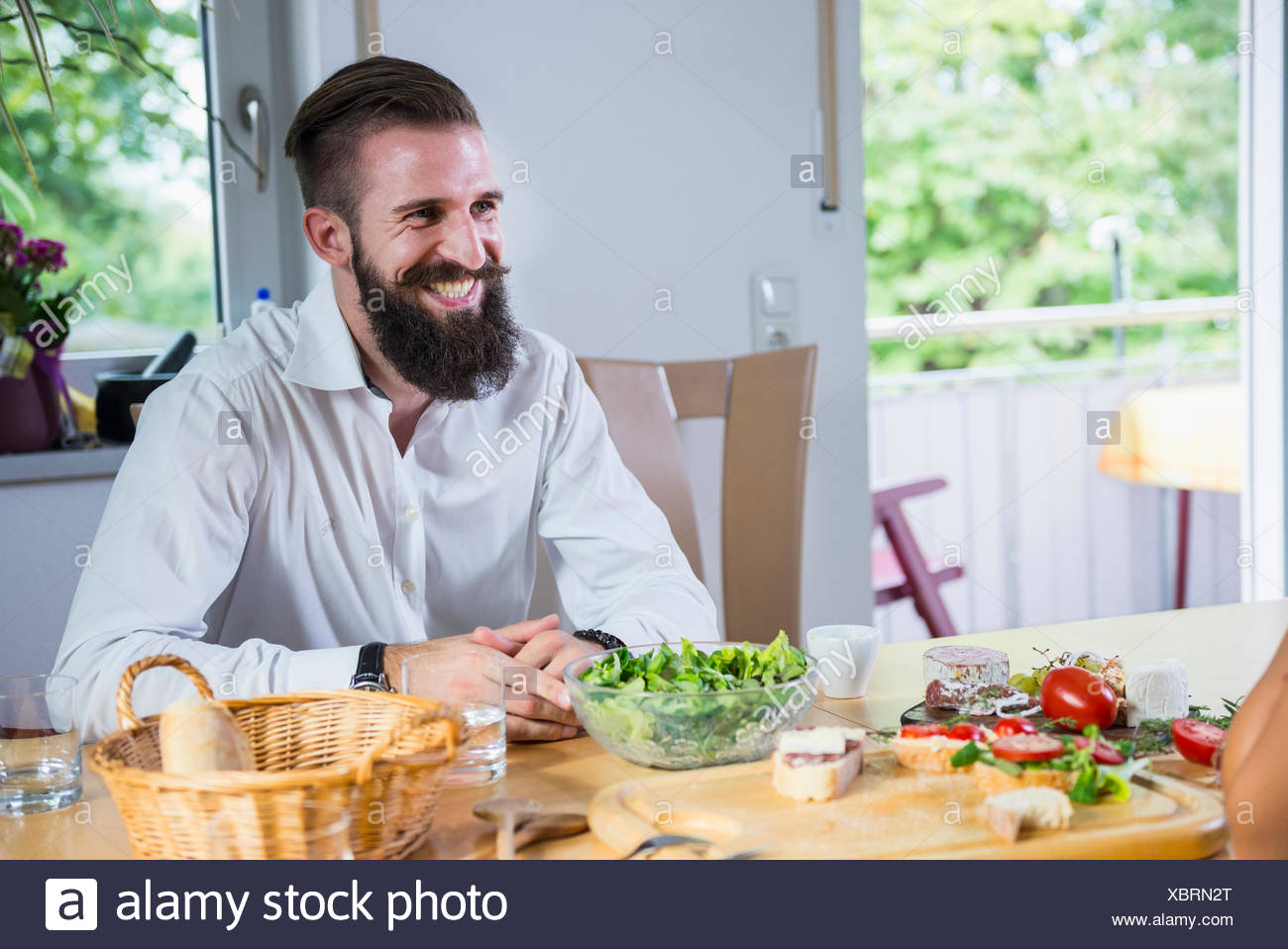 Young man sitting at kitchen table and smiling, Bavaria, Germany - Stock Image