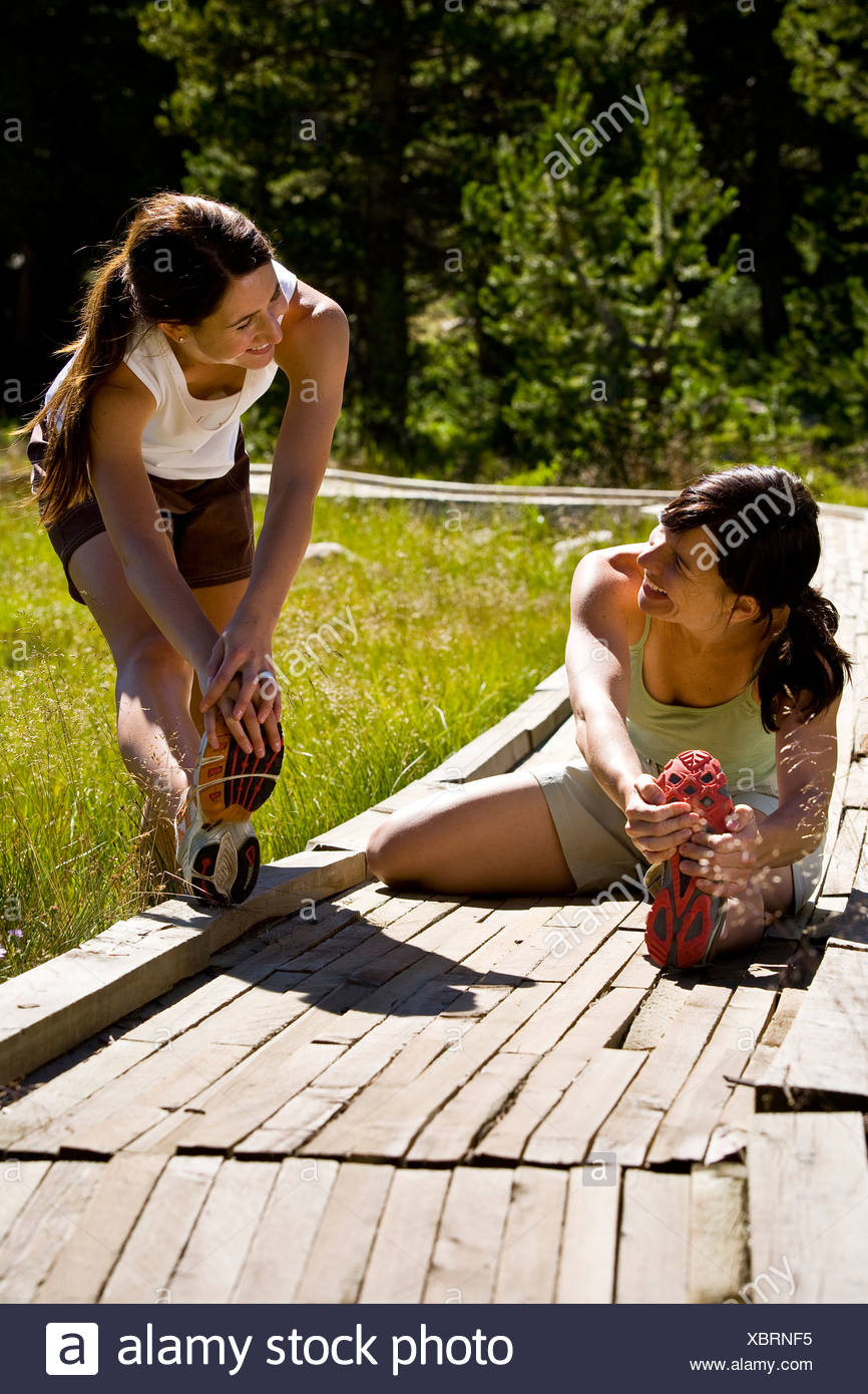 Two women stretch prior to running in Utah's Uinta Mountains. - Stock Image