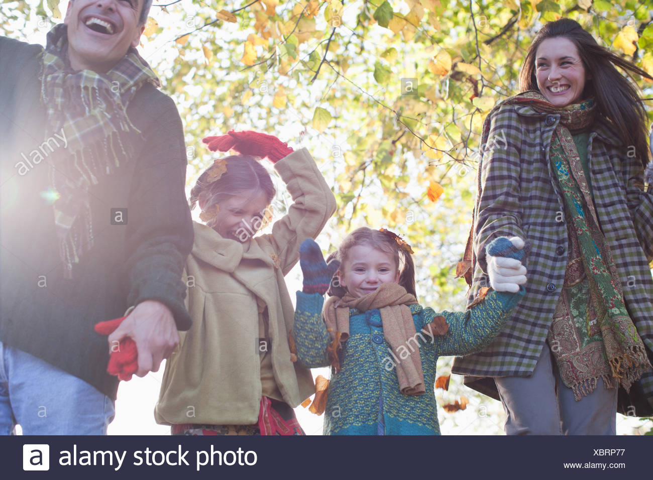 Family laughing and holding hands outdoors - Stock Image