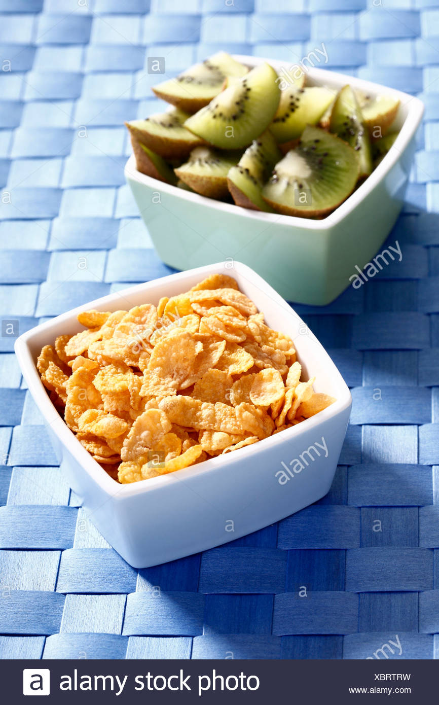 Cornflakes and kiwi slices in bowls Stock Photo