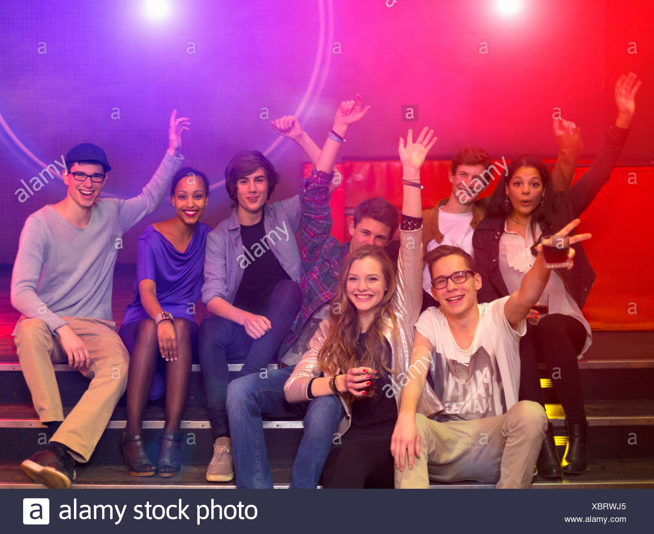 Group of teenagers and young adults at party holding drinks and raising arms - Stock Image