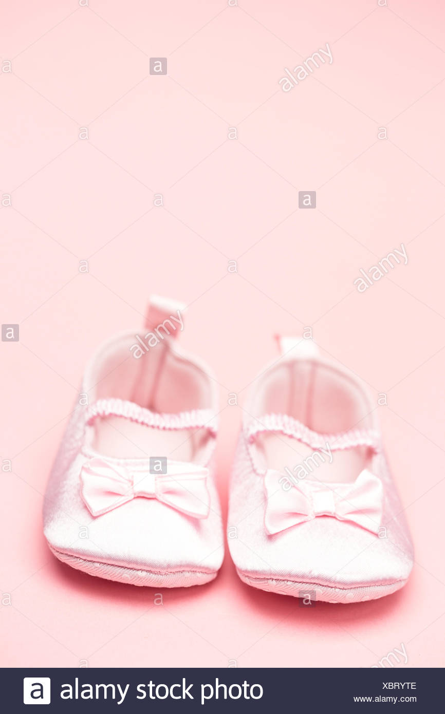 Baby girls pink booties with copy space - Stock Image