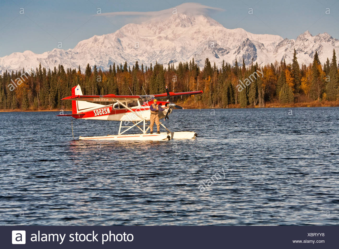 Flyfisherman fishing off of the float of a Cessna 185 floatplane on