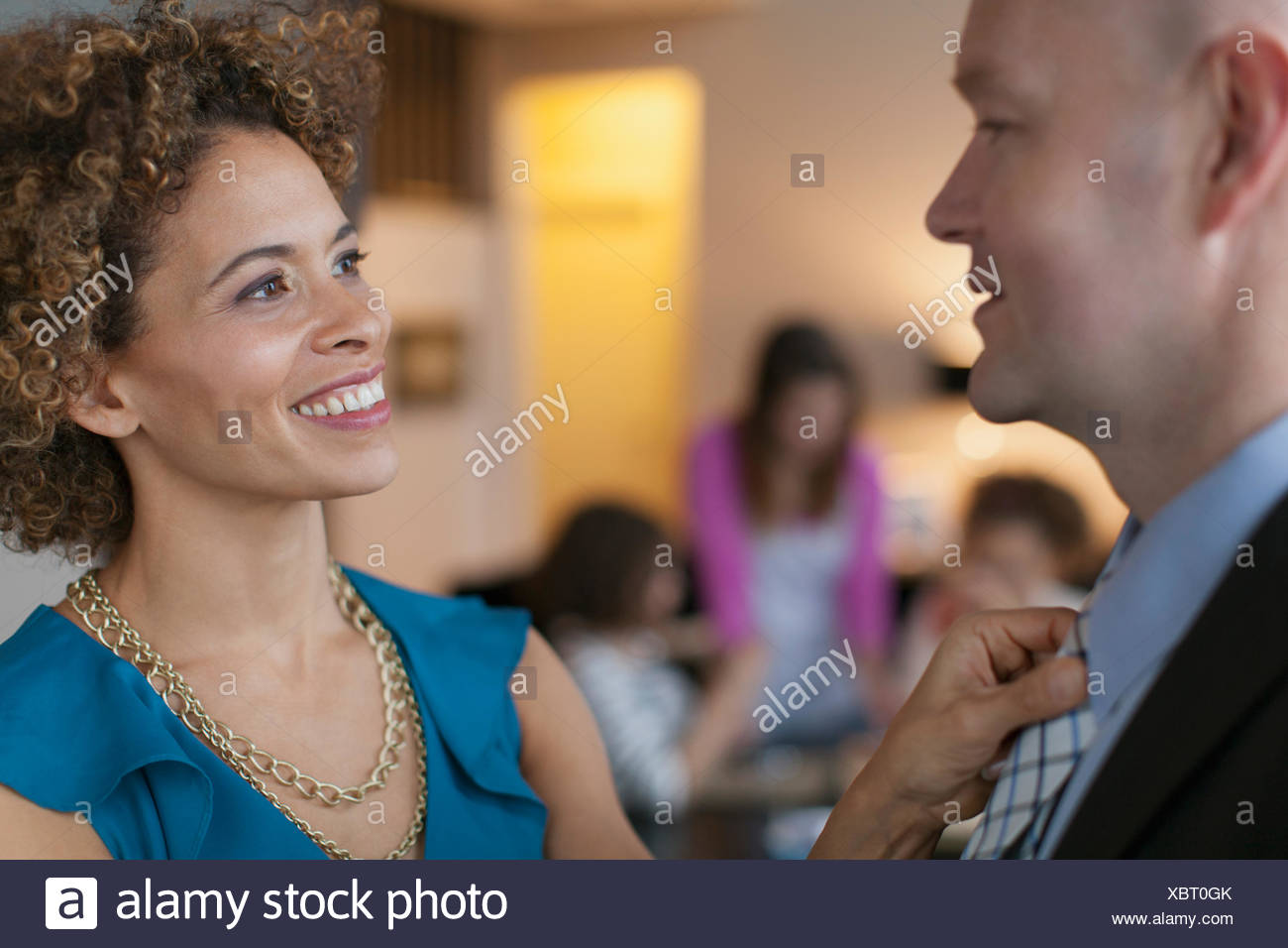 Wife adjusting husbands necktie before going out. - Stock Image