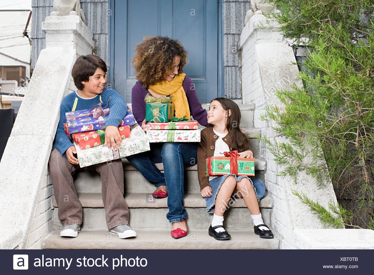 Mother and children sat on a step holding gifts - Stock Image