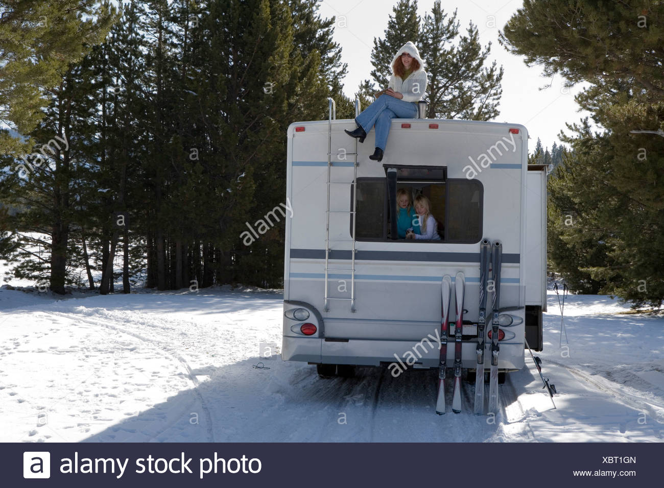 Mature Woman Sitting On Top Of A Recreational Vehicle With Her Two Daughters Inside It