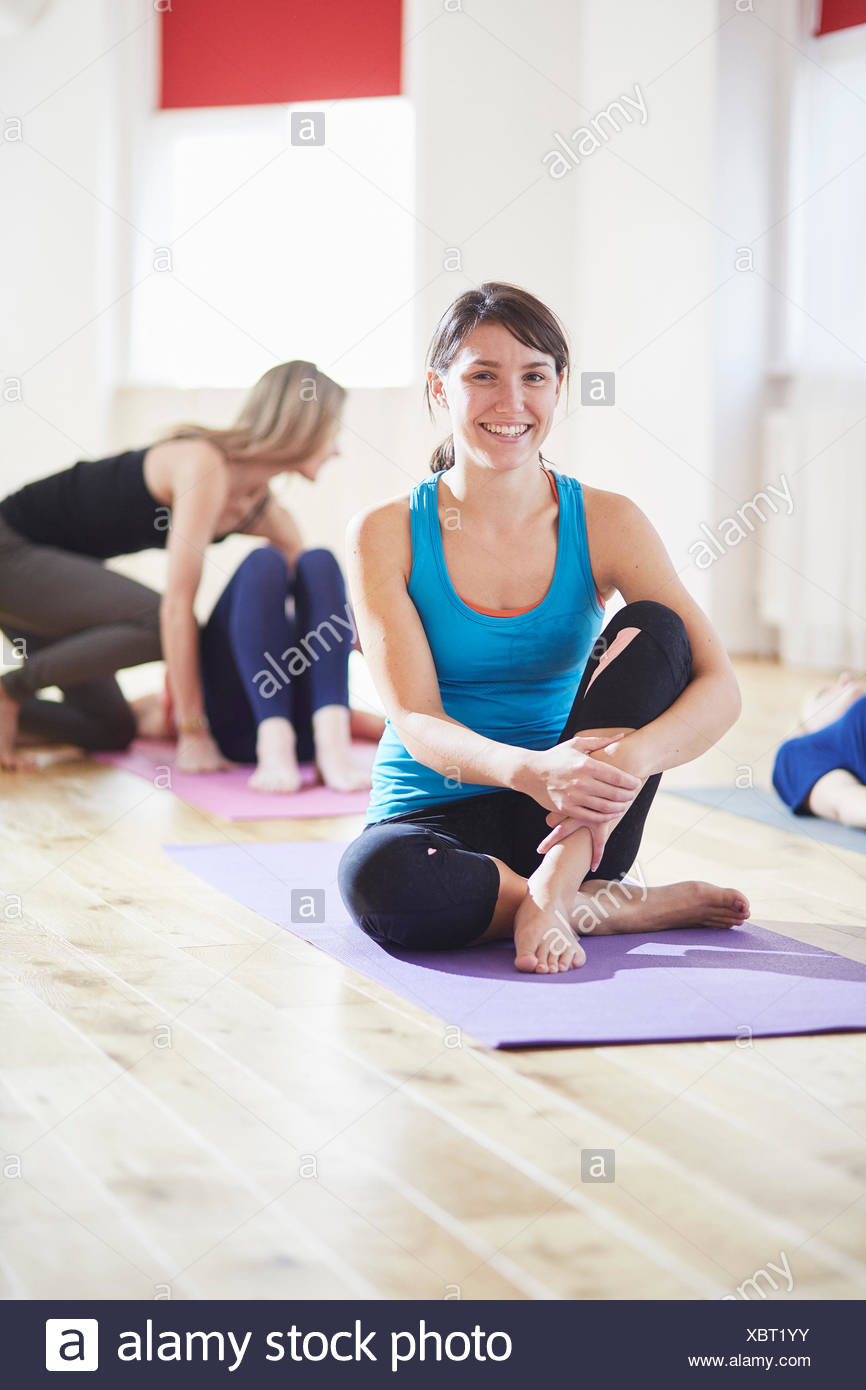 Portrait of young woman sitting on floor in pilates class - Stock Image