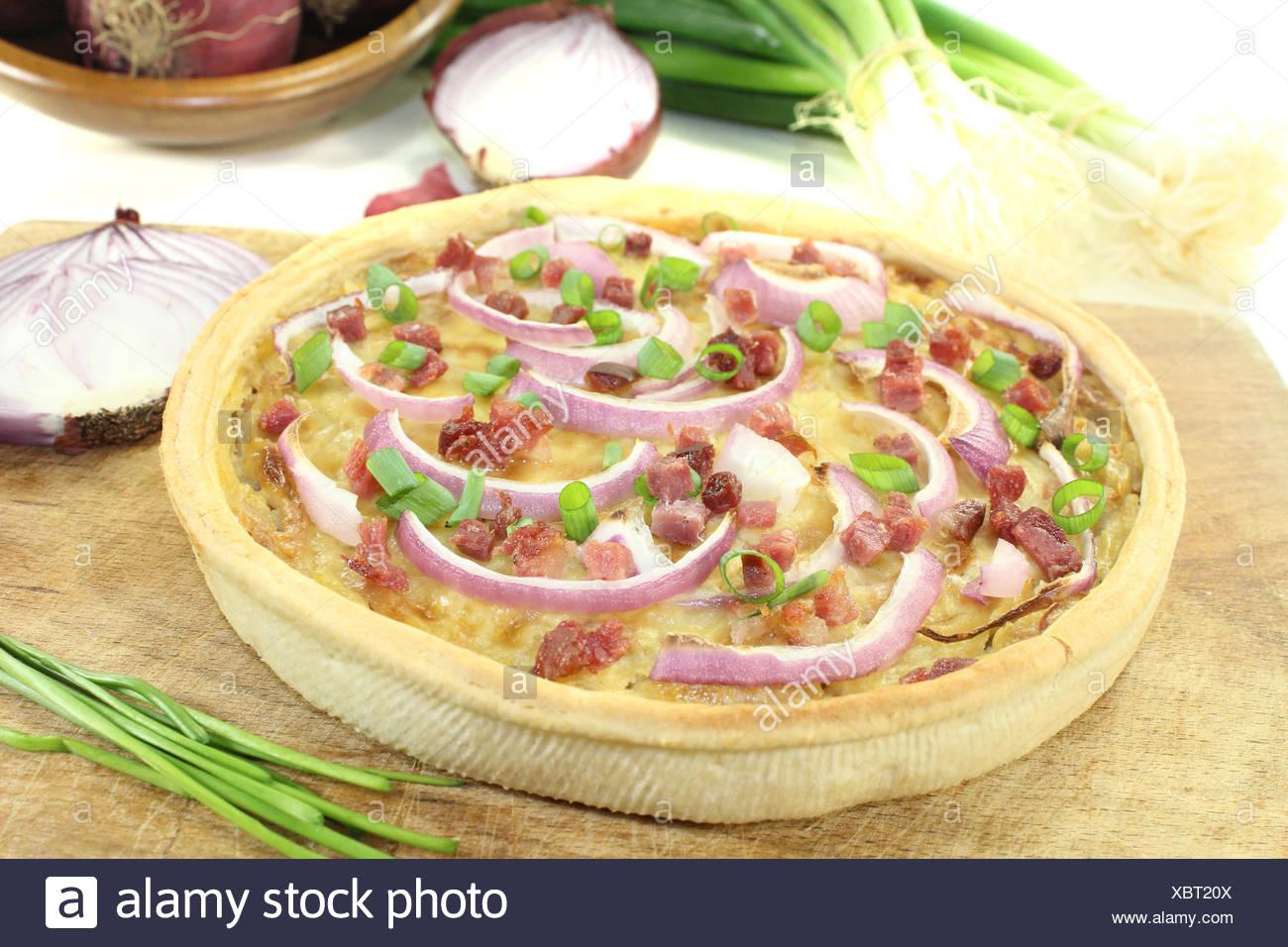 Zwiebelkuchen mit Schinkenspeck vor hellem Hintergrund Stock Photo