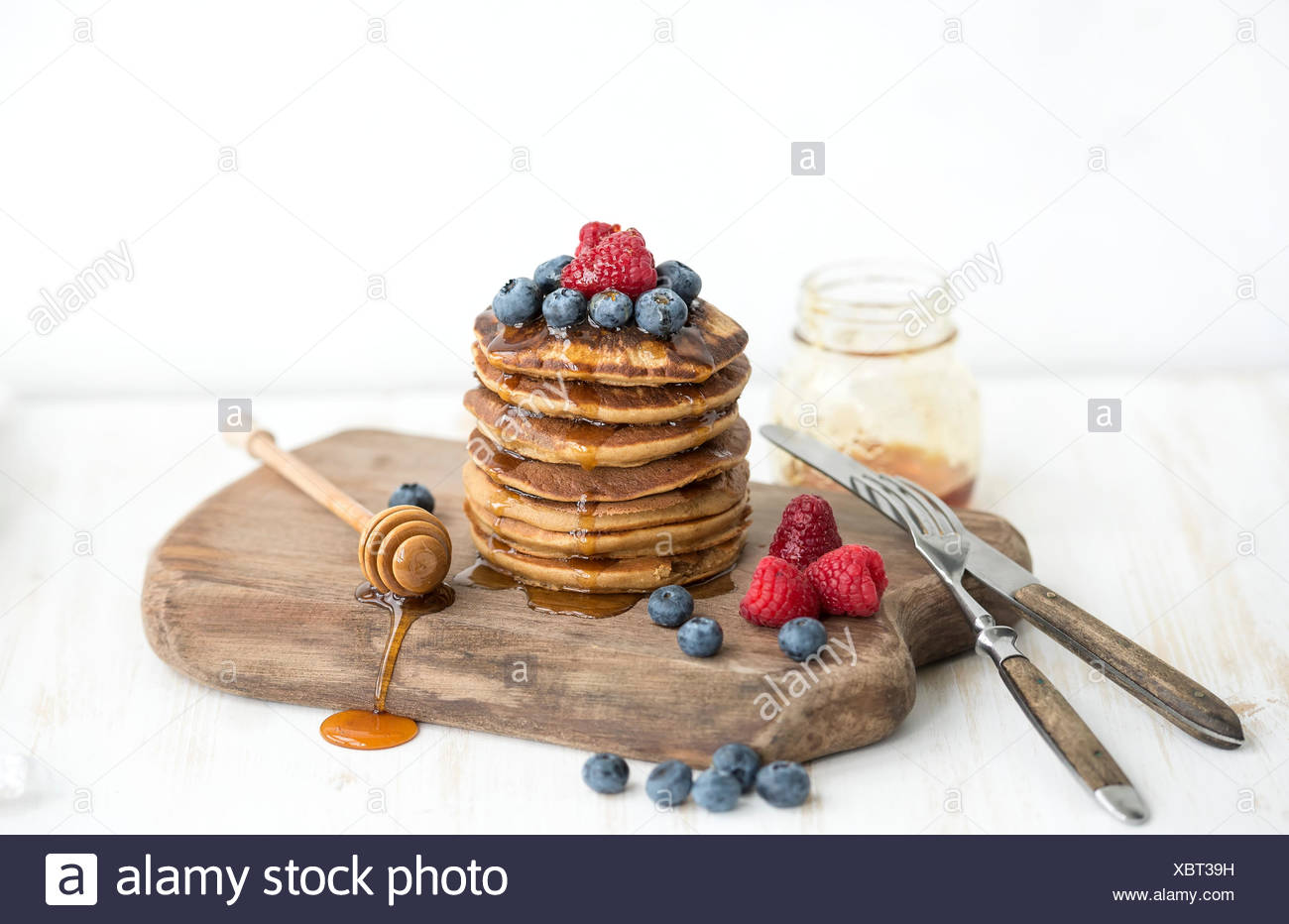 Homemade pancakes with fresh garden berries, honey on wooden board over white painted wooden background, selective focus, horizo - Stock Image