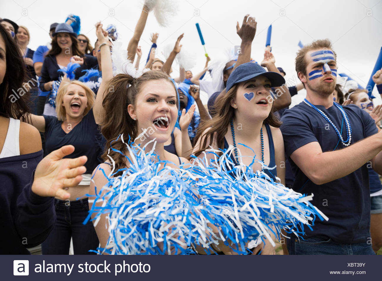 Enthusiastic crowd in blue cheering at sports event - Stock Image