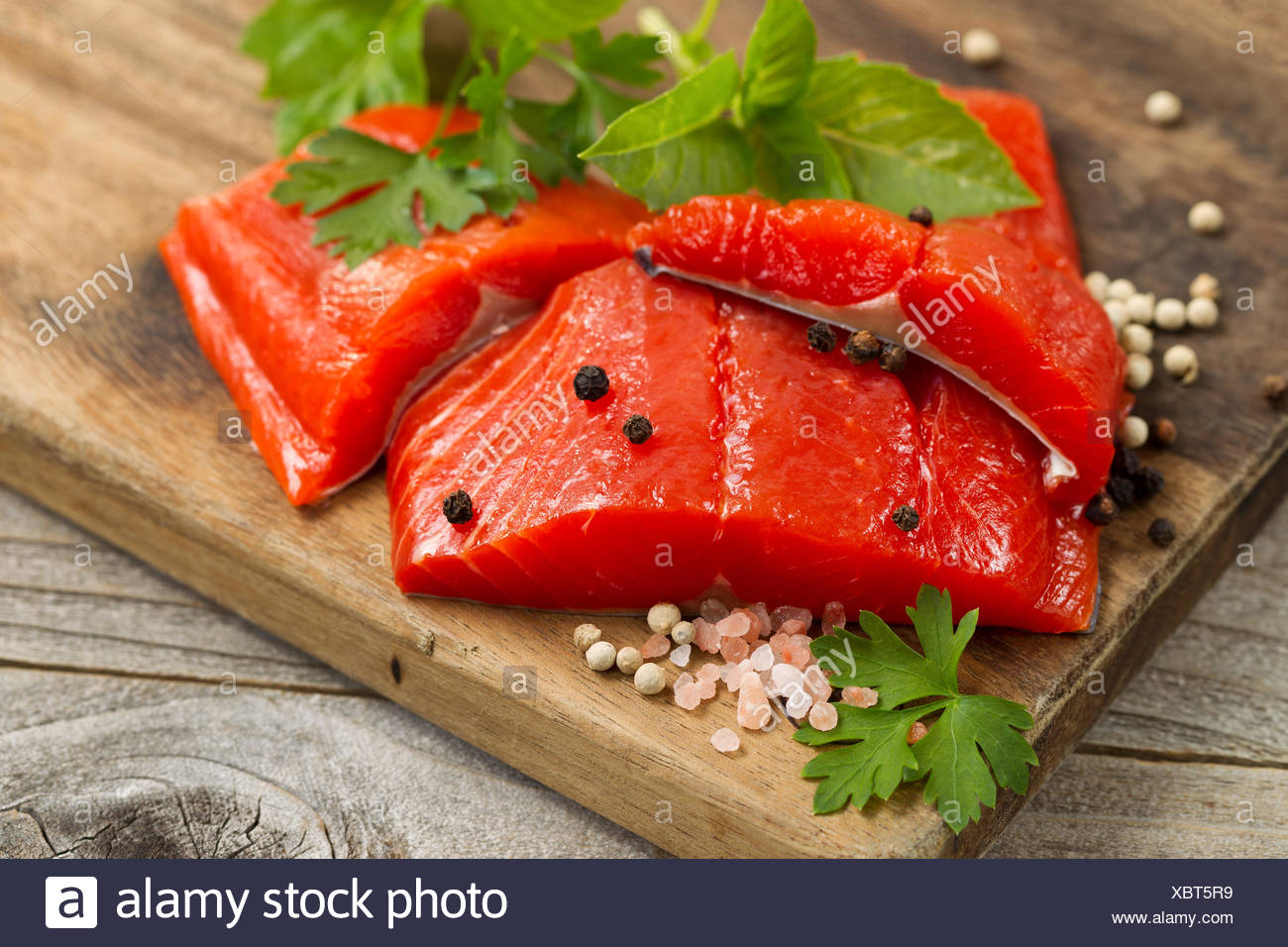 Fresh bright red Copper River Salmon fillets on rustic wooden server with spices and herbs - Stock Image