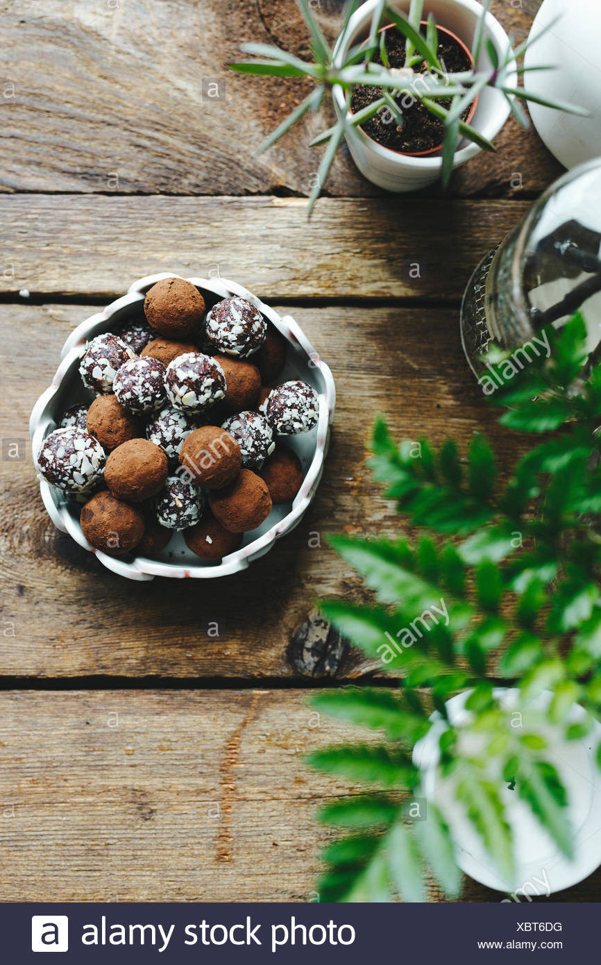 Chocolate truffles covered in nuts, on a wooden table. Stock Photo