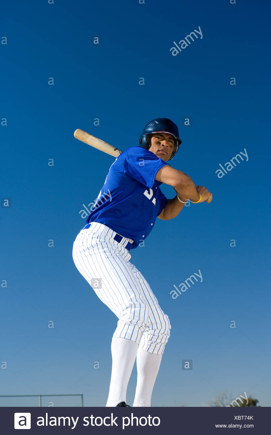 Baseball batter standing against clear blue sky, preparing to hit ball, front view, low angle view Stock Photo