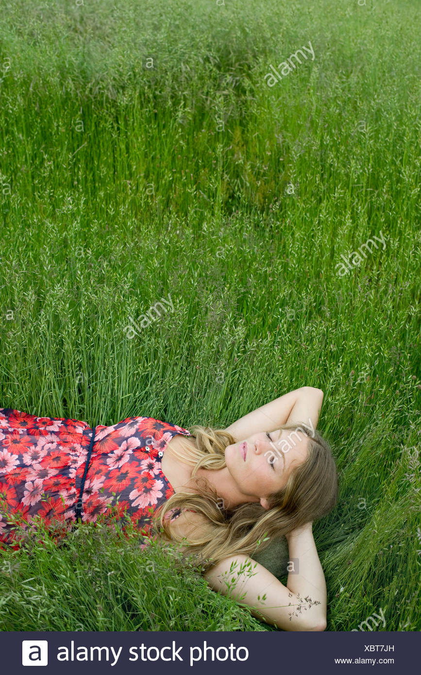 Young woman napping in tall grass - Stock Image