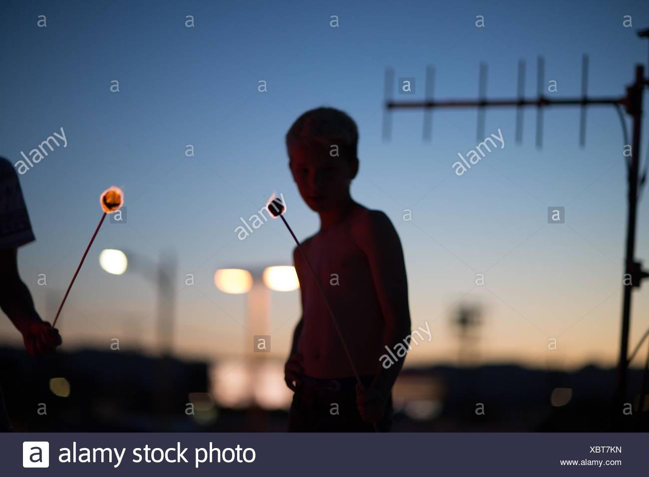 Silhouette of teenage boys holding smoldering marshmallows on sticks - Stock Image