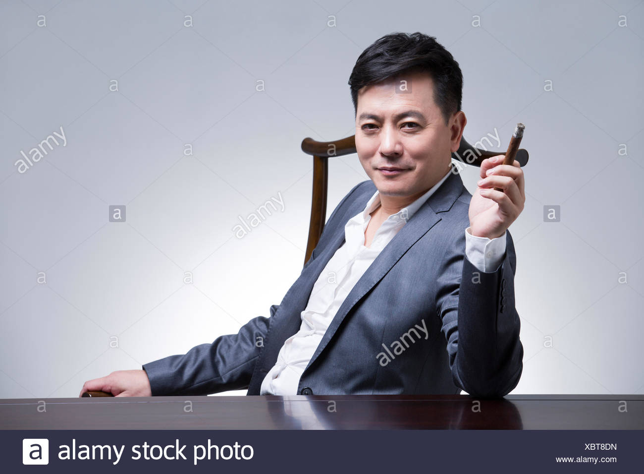 Mature businessman with cigar Stock Photo