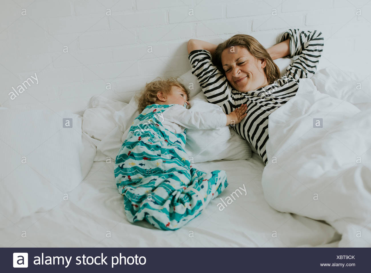 Mother and little daughter in bed - Stock Image