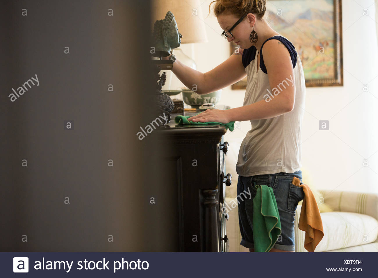 Young woman cleaning surfaces with green cleaning products Stock Photo