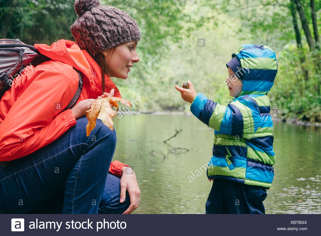 Mother and son exploring stream in forest, Vancouver, British Columbia, Canada - Stock Image