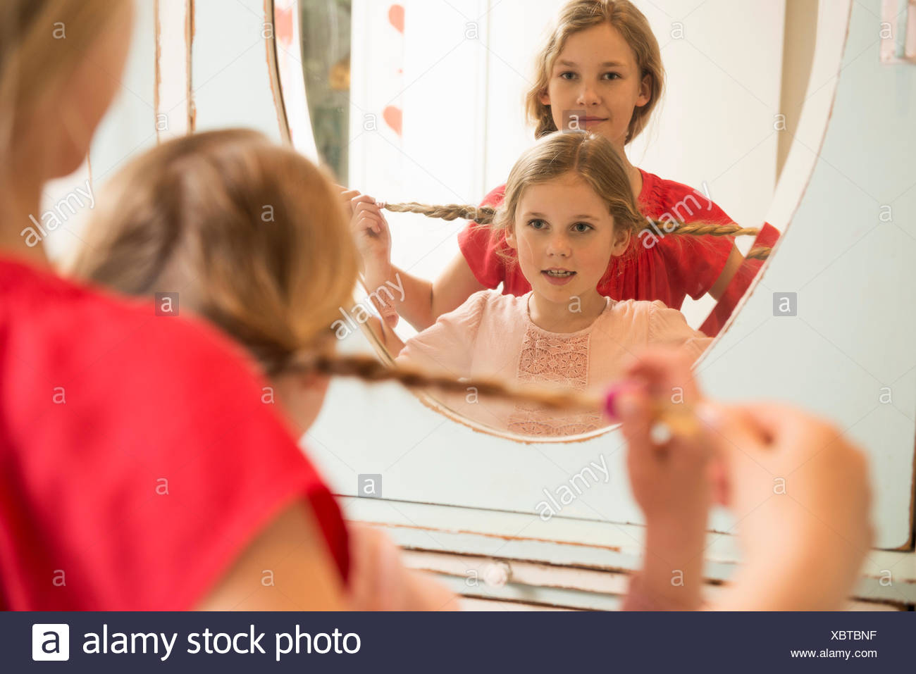 Sisters holding up plaits in bedroom mirror - Stock Image