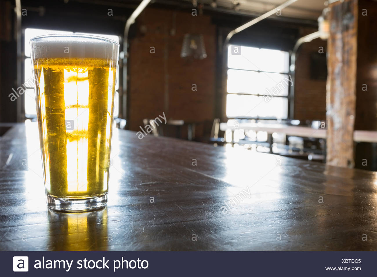 Pint of beer on counter in empty pub - Stock Image