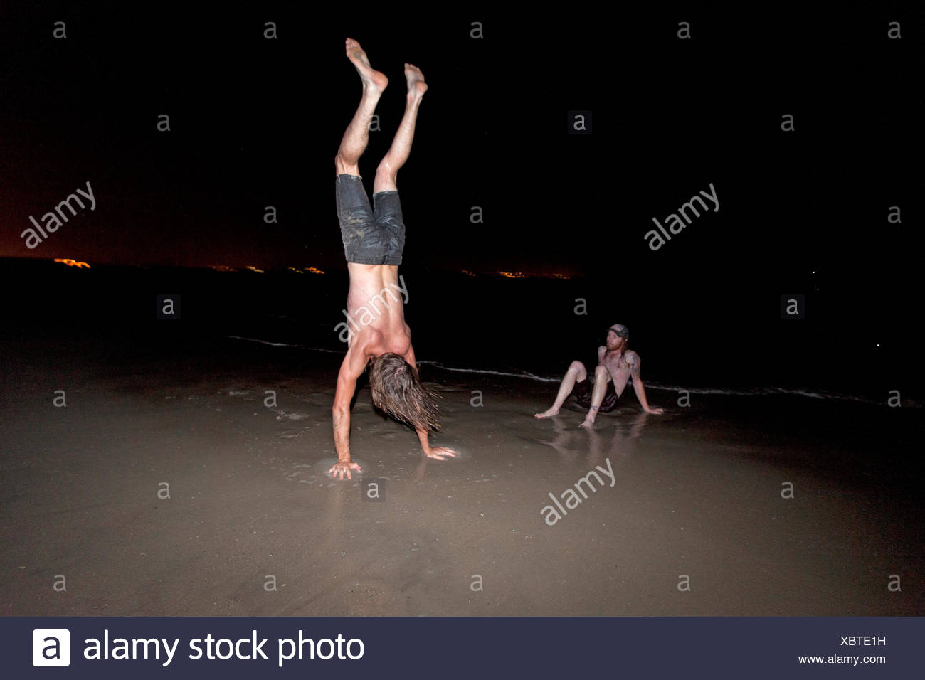 Friends playing on a beach at night - Stock Image