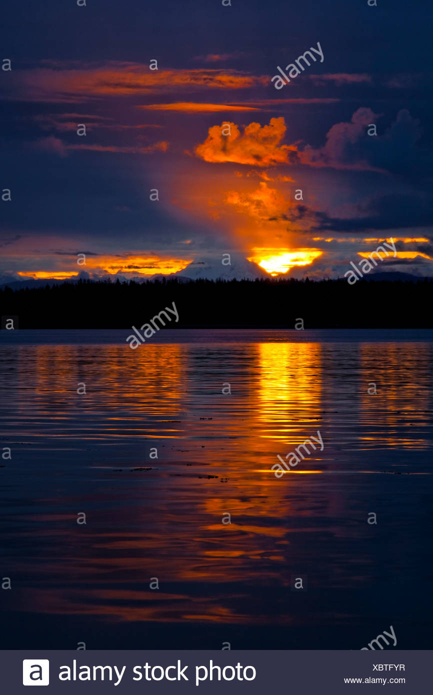Dramatic sunset behind Fairweather Mountains and reflecting off water in Bartlett Cove, Glacier Bay National Park & Preserve - Stock Image
