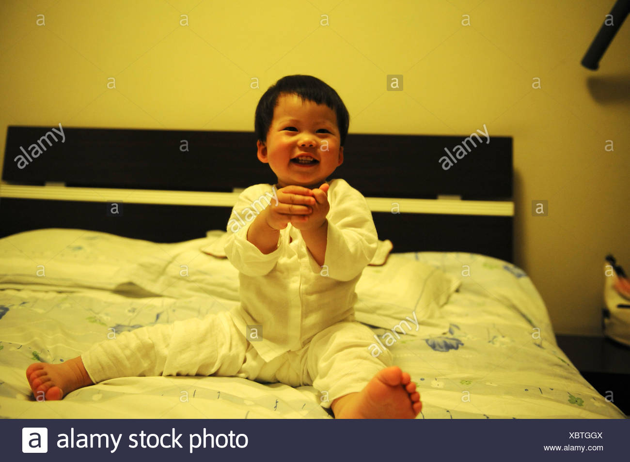 Chinese baby girl giggling on bed, Chengdu, Sichuan Province, China - Stock Image