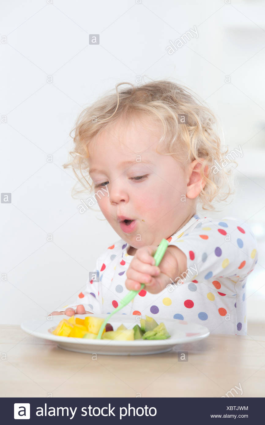 Determined baby eating fruit with fork - Stock Image