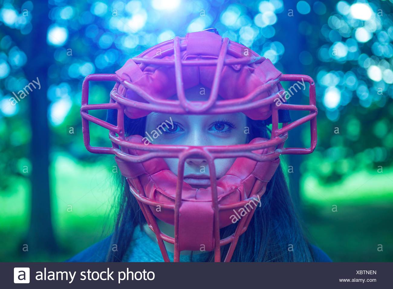 Portrait of staring teenage girl in park wearing red umpire mask - Stock Image