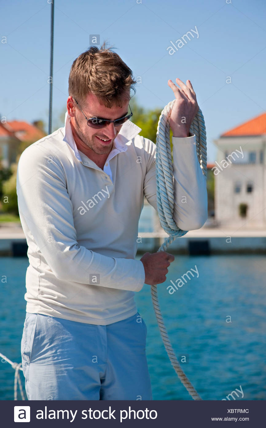 Croatia, Zadar, Young man coiling rope on sailboat in harbour - Stock Image