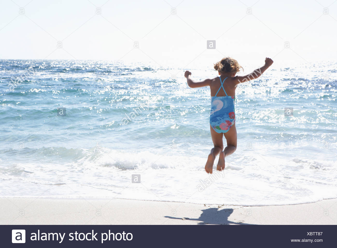 Girl 3 5 wearing swimsuit jumping above surf on sandy beach rear view sea shimmering in sunlight - Stock Image