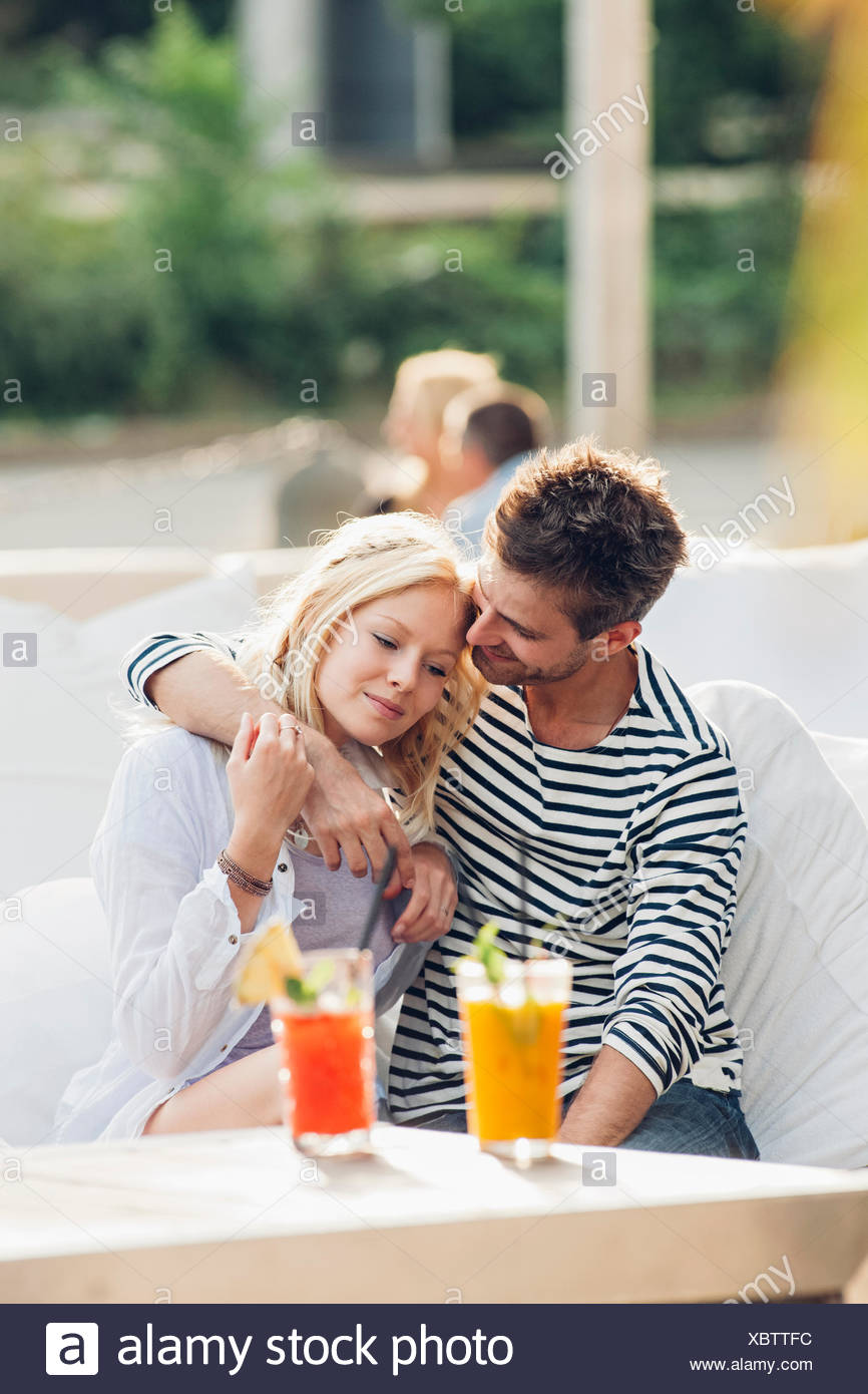 Young couple sitting together in an outdoor lounge - Stock Image