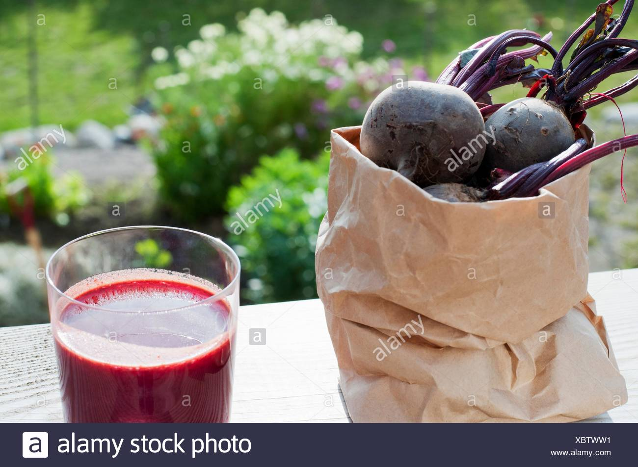 Bag of organic beetroot and glass of beetroot juice on garden table - Stock Image