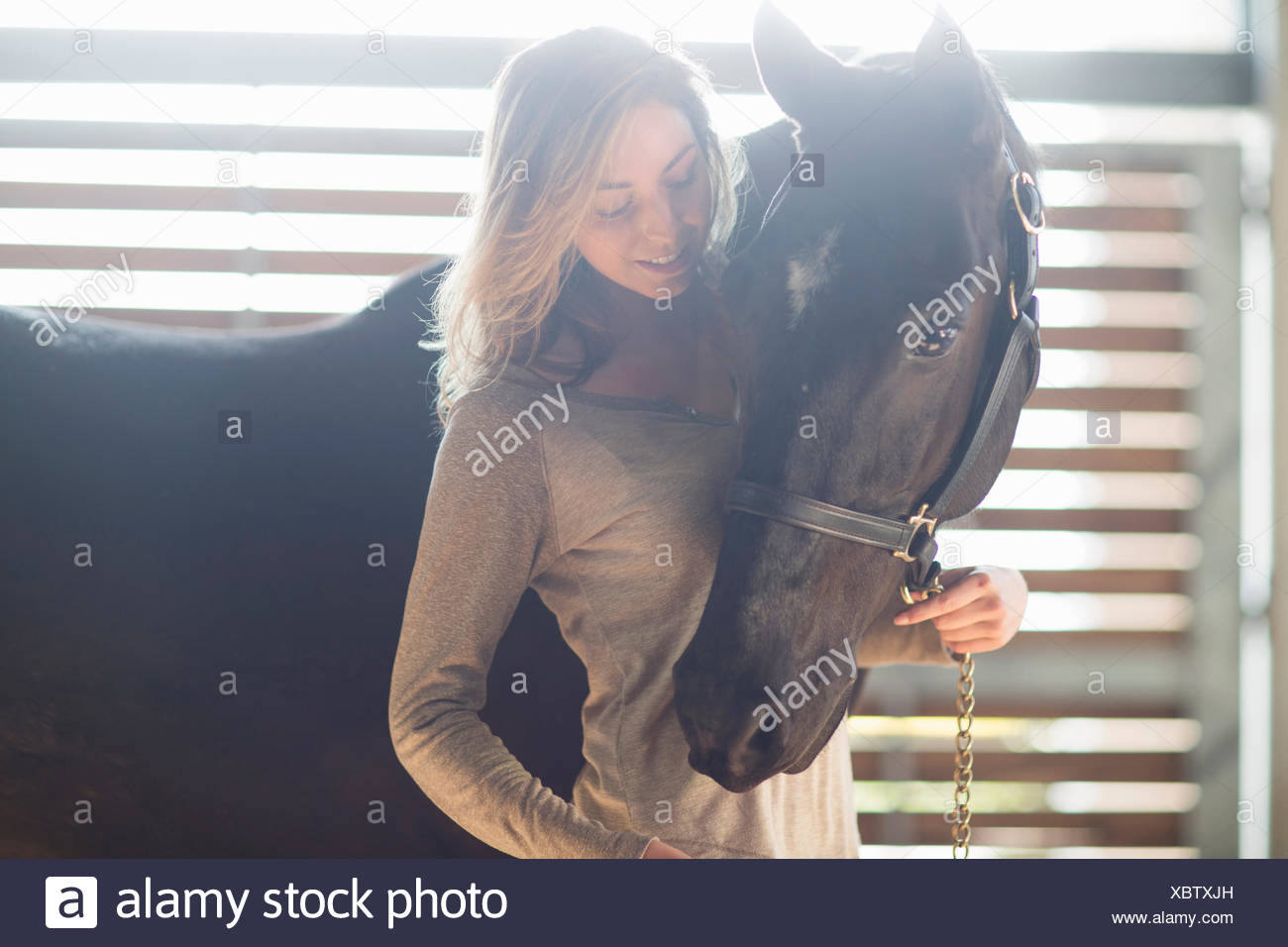 Tender portrait of young woman with black horse - Stock Image