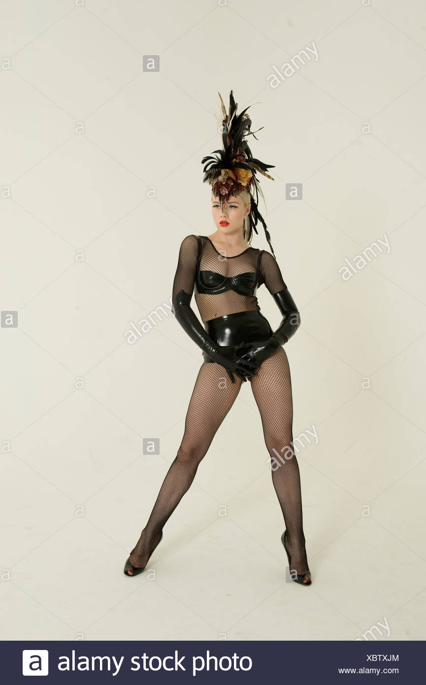 b773b47ae6e12 Pinup woman wearing fishnet stockings and leather posing over colored  background - Stock Image