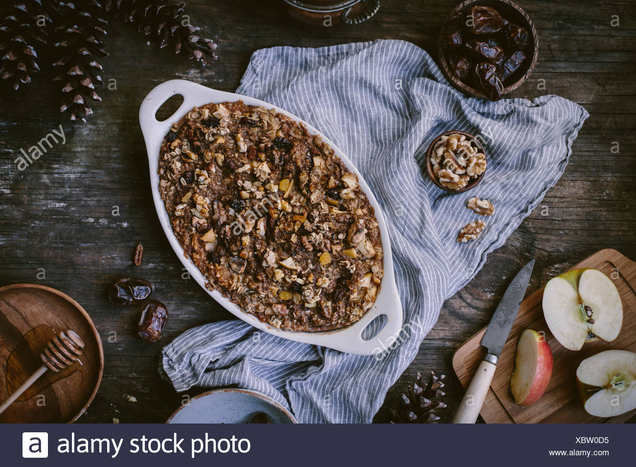 Baked oatmeal with apples, dates, bananas, and walnut is just out of the oven, about to be served and displayed on a reclaimed w - Stock Image
