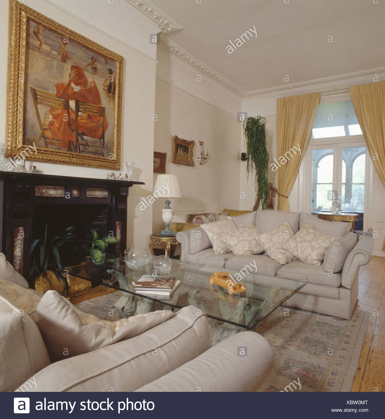 Cream Sofas And Modern Glass Table In Traditional Living