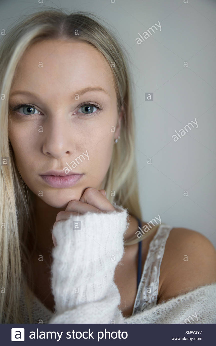 Portrait serious blonde woman with hand on chin - Stock Image