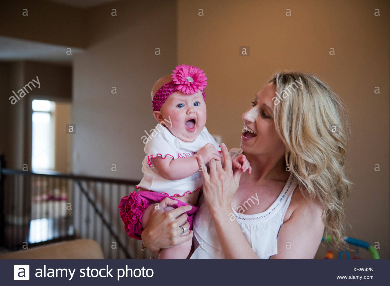 A mother tries to cheer up her fussy young child. - Stock Image
