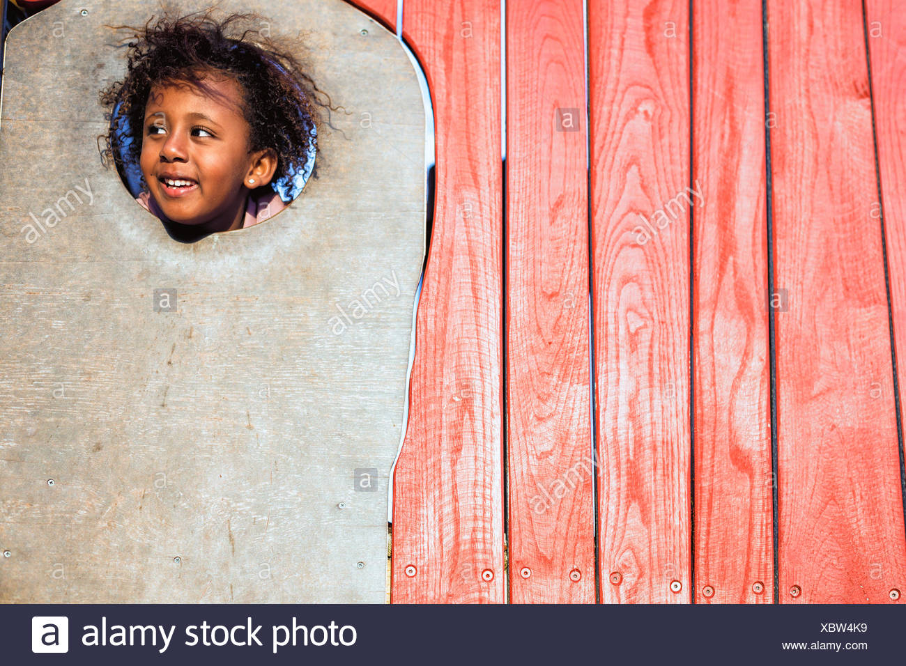 Smiling girl poking her head through a hole in the wall, Perth, Australia - Stock Image