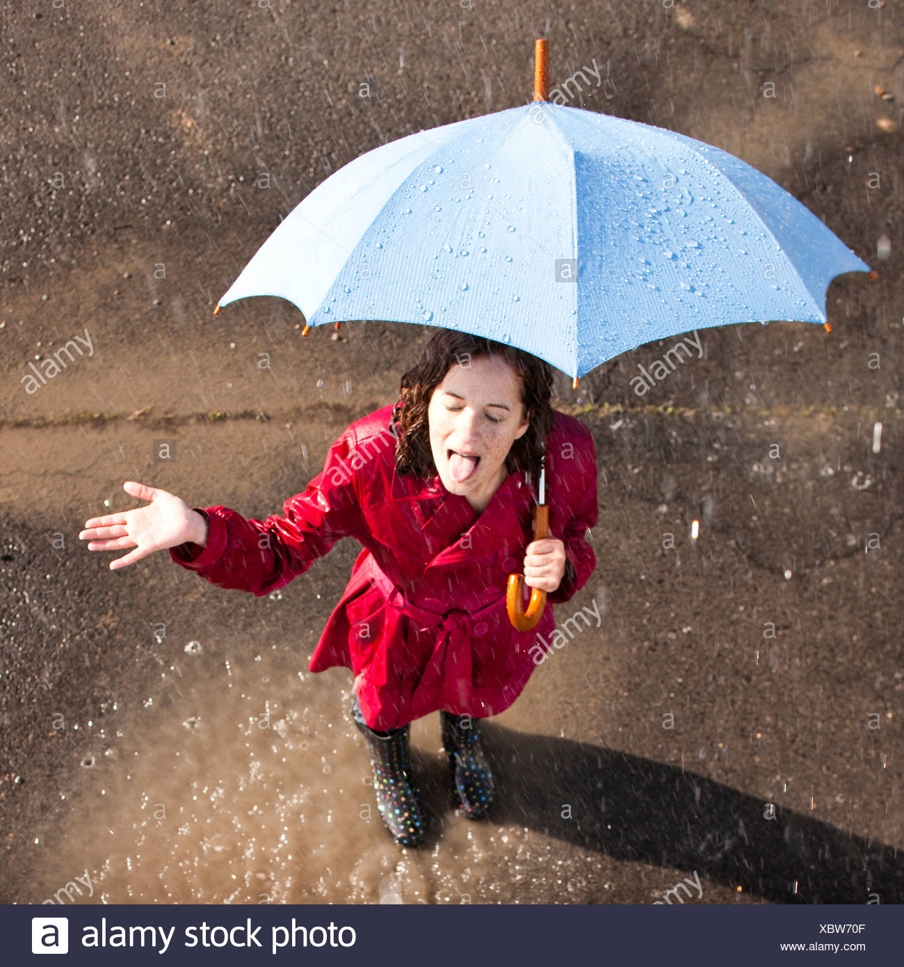 Young woman standing in rain holding umbrella - Stock Image