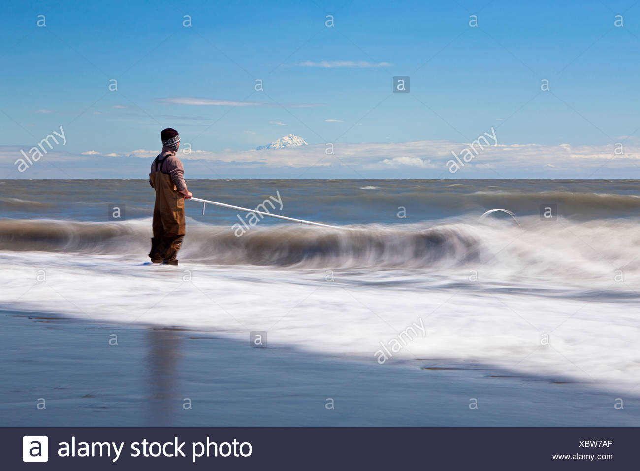 Surf zone with a fisherman on the beach in Kenai on the Kenai Peninsula with Mount Redoubt volcano in the Cook Inlet, Alaska - Stock Image