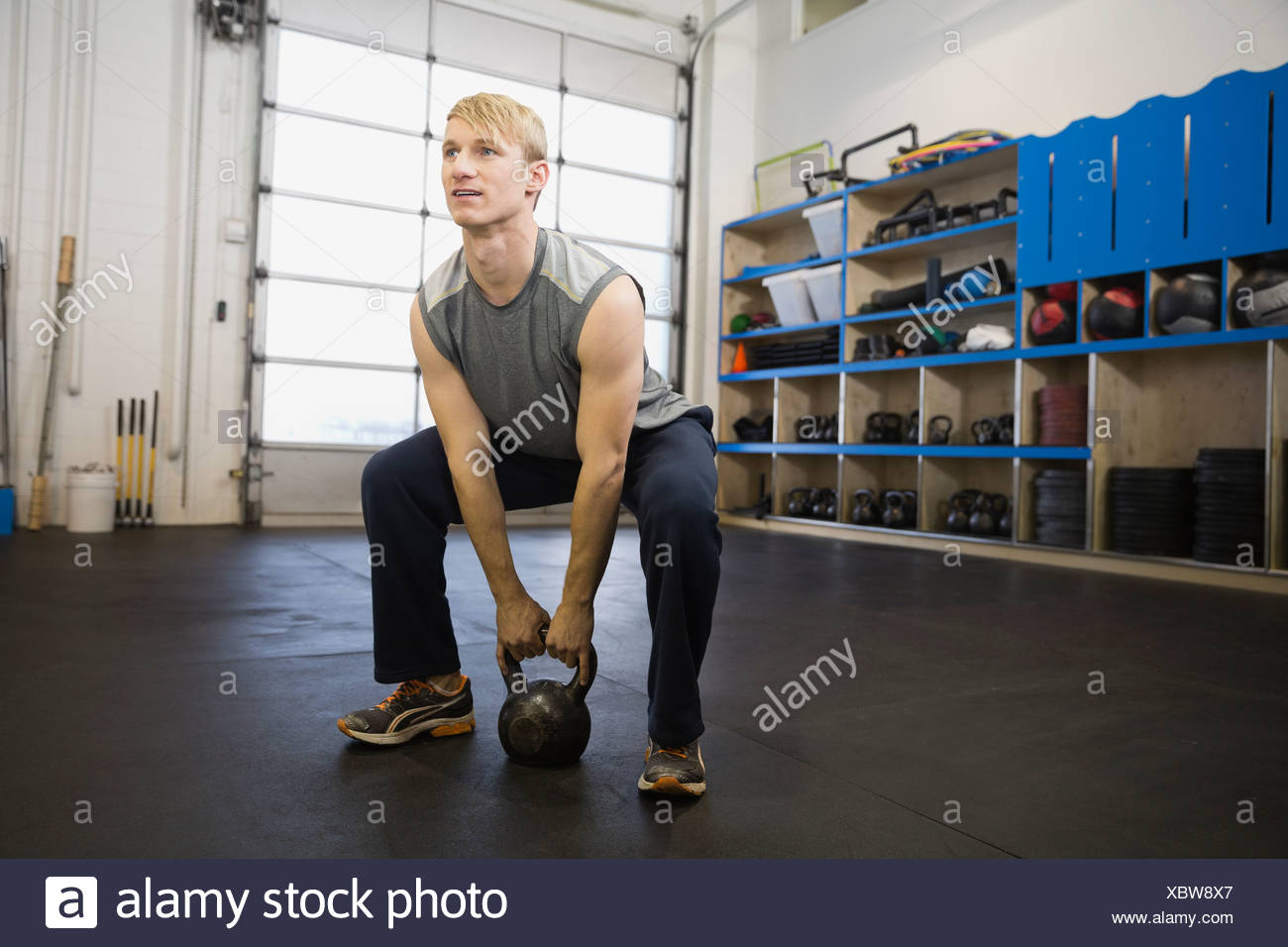 Man exercising with kettlebells - Stock Image