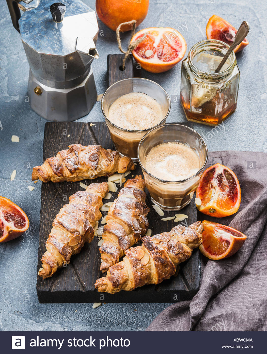 Italian style home breakfast. Latte coffee almond croissants and red bloody oranges on dark wooden serving  board over concrete - Stock Image