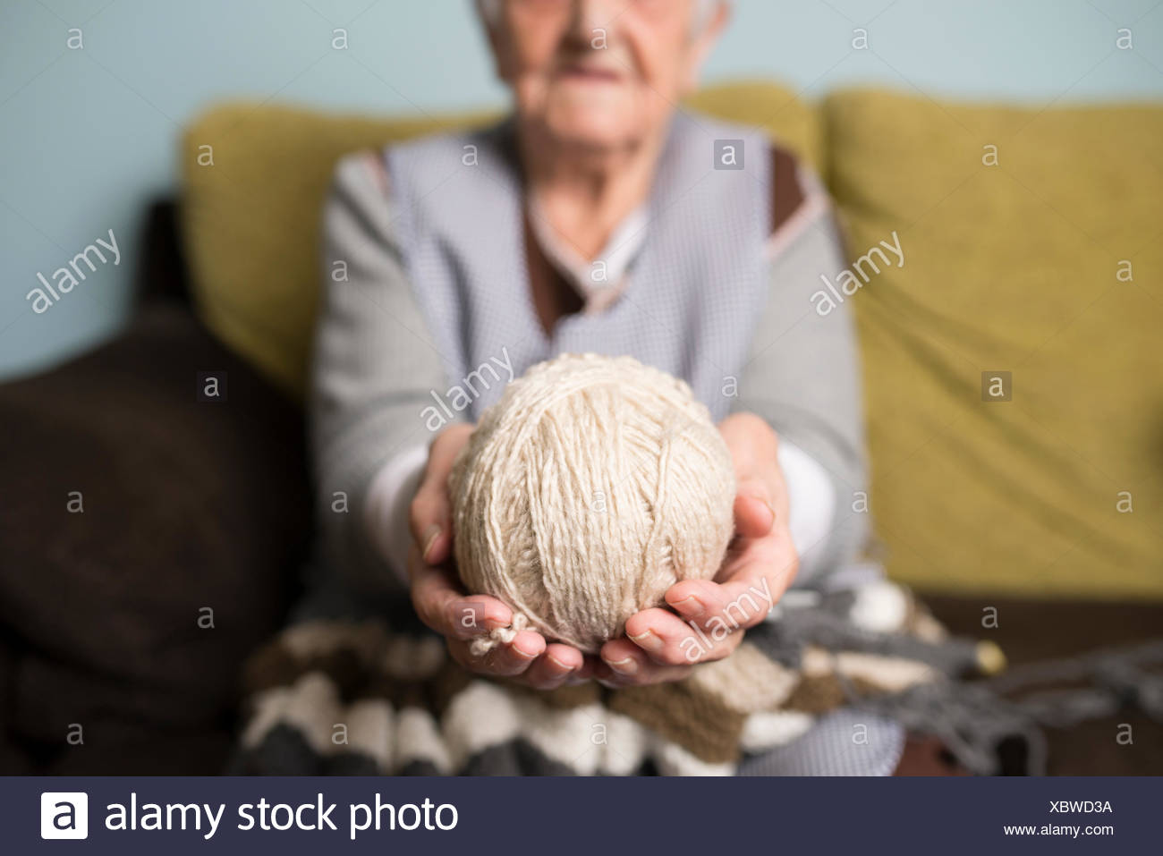 Hands of senior woman holding ball of wool Stock Photo