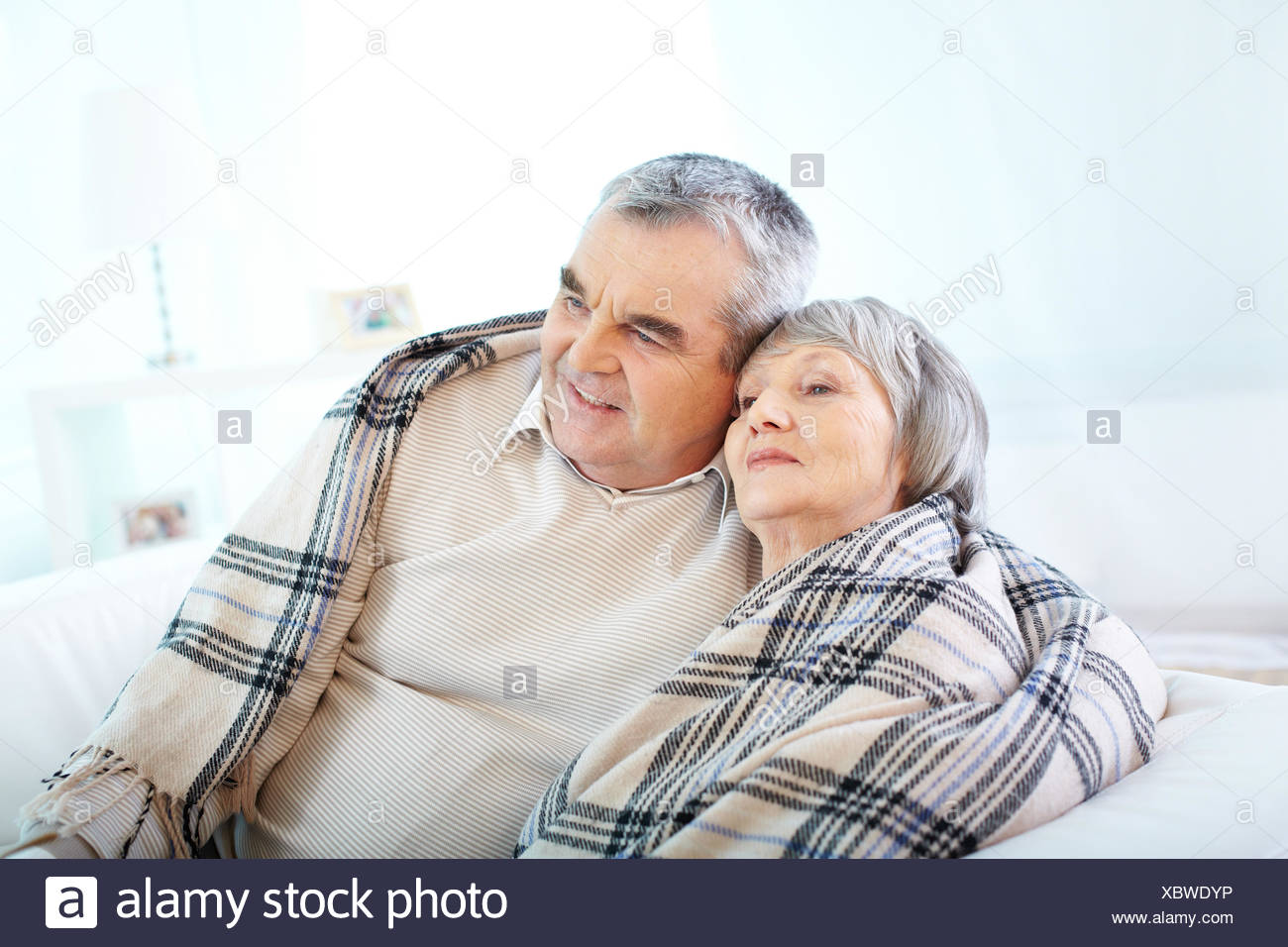 Portrait of a senior couple wrapped in plaid - Stock Image