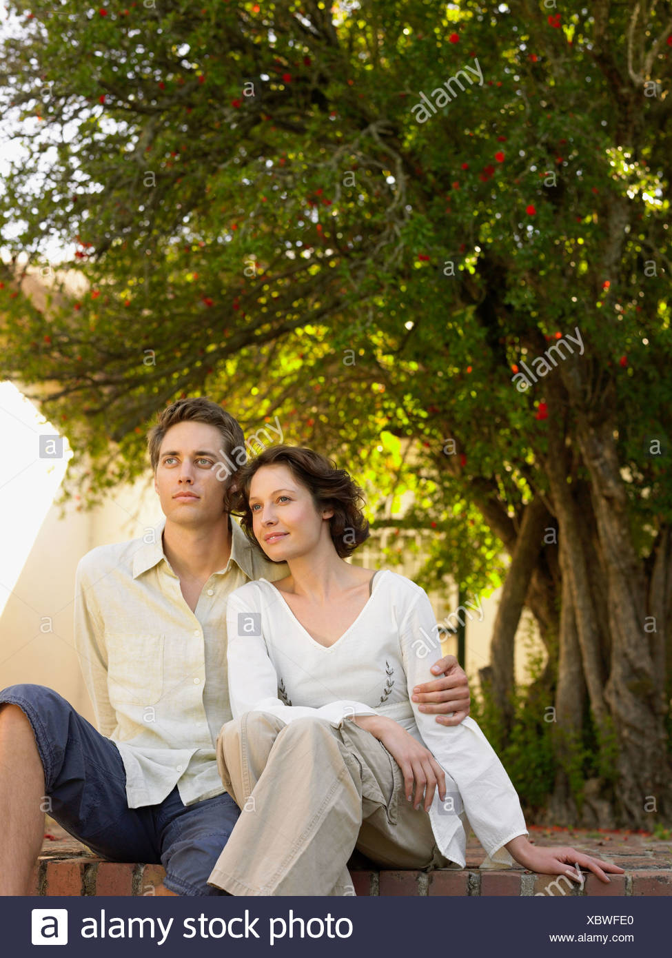 Portrait of couple sat outdoors - Stock Image