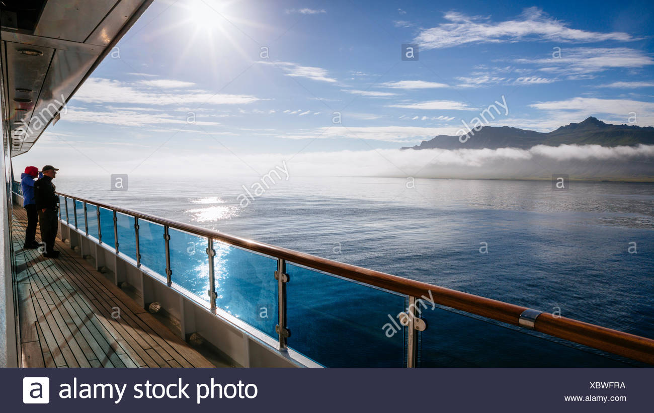 Two ship passengers looking at view of east coast of Iceland - Stock Image