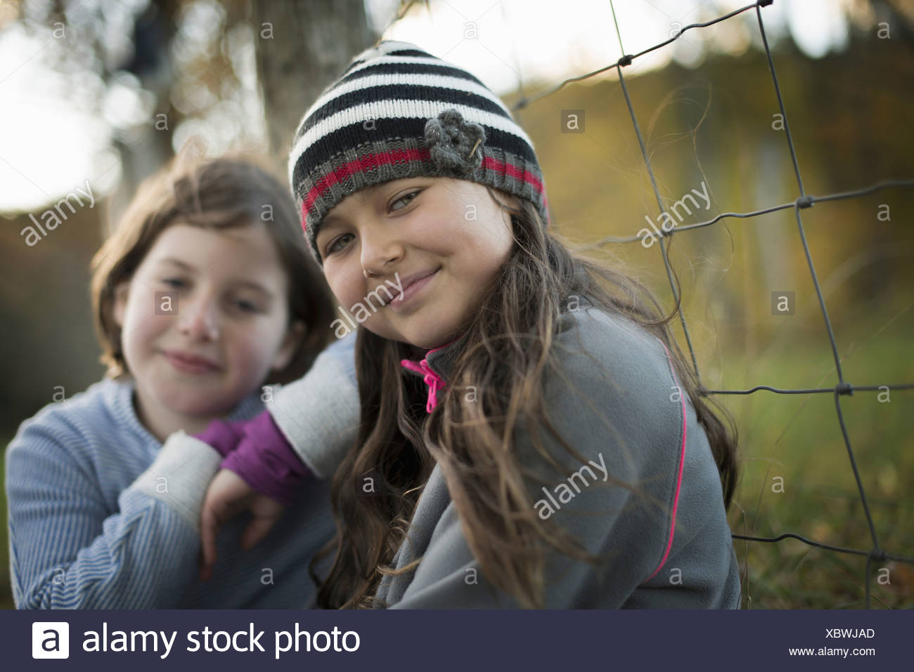 Two young girls side by side outdoors on a farm Leaning on a fence post - Stock Image